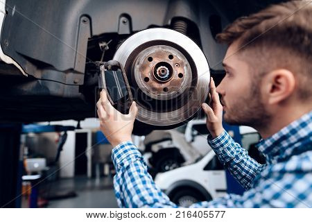 A young man works at a service station. The mechanic is engaged in repairing the car. A young mechanic is repairing the disc brake.