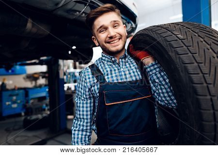A young man works at a service station. The mechanic is engaged in repairing the car. A young mechanic posing with tires from the car.