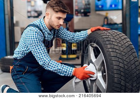 A young man works at a service station. The mechanic is engaged in repairing the car. A young mechanic works with a car wheel.