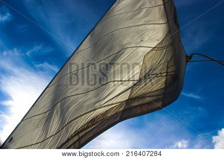 white sail flapping against a blue sky