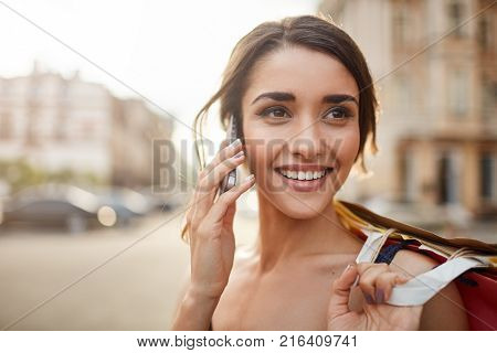 Close up portrait of beautiful joyful young caucasian woman with dark hair smiling with teeth, looking aside with happy and calm face expression, talking on phone with friend, holding shopping bags in hand