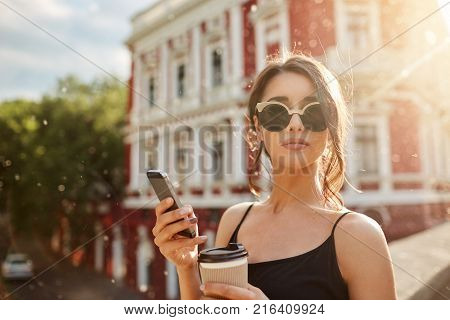Summer days. Close up portrait of attractive skinny feminine caucasian woman with dark hair in tan-glasses and black dress, waiting for boyfriend that being late for date, chatting with friend by smartphone, drinking coffee, looking in camera with calm ex