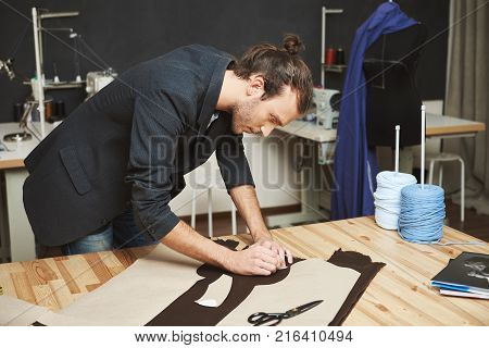 Portrait of manly good-looking adult male clothes designer with stylish hairstyle in black suit cutting out parts of future dress from fabric. Man concentrated on work