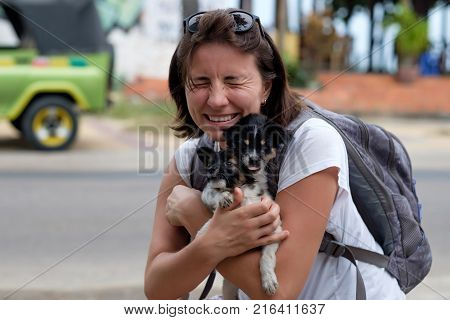 Young woman hugs two small puppies. She finds them in animal shelter. Concept of having new pet friend