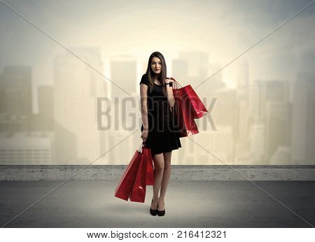 Attractive lady in black holding red shopping bags standing in front o urban landscape with tall buildings concept
