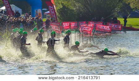 GRAFHAM, CAMBRIDGESHIRE, ENGLAND - MAY 21, 2017:  Triathlon swimmers entering open water swim stage.