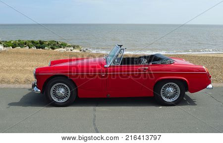 FELIXSTOWE, SUFFOLK, ENGLAND -  MAY 07, 2017: Classic  Red  MG Roadster  Car  parked on seafront promenade with sea in background.