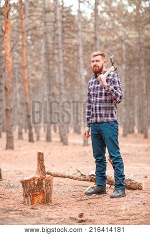 A red-haired man, a woodcutter, stands in a blue checkered shirt and blue trousers with an ax in his hand next to the wood. Outdoors.