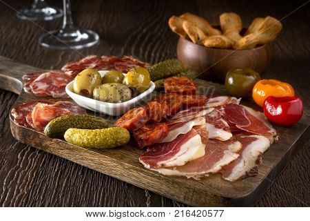 A delicious charcuterie assortment of meat olives gherkins and pickled peppers with breadsticks on a wooden background.