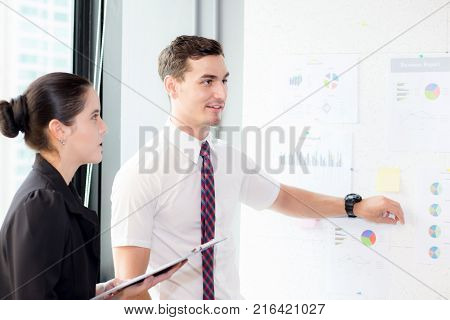 young businessman pointing towards graph and businesswoman holding clipboard with present profit while giving presentation in office teamwork concept.
