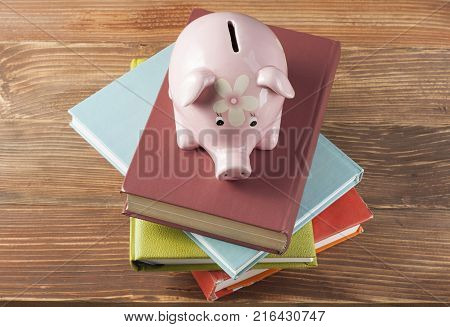 Piggy bank with colorful books on wooden table. Funding of education concept