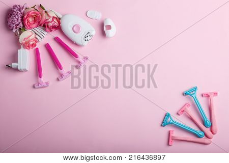 Female epilator and four disposable pink razors with roses, lie on a pink background in the upper left corner, in the lower right corner are five disposable razors, free space for text.