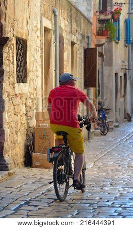 ROVINJ, ISTRIA, CROATIA - JUNE 18, 2017: Man on bicycle  riding through the streets of the old town Rovinj  Istria Croatia.