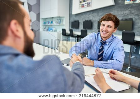 Confident young business partners in formalwear greeting each other with firm handshake while sitting at spacious boardroom