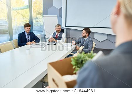 Group of hard-working white collar workers in classical suits sitting at boardroom table and analyzing results of accomplished work, unrecognizable female colleague holding cardboard box in hands