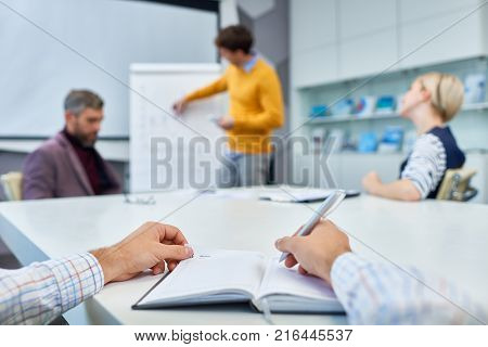 Close-up shot of unrecognizable manager taking necessary notes while sitting at boardroom table during working meeting, focus on foreground
