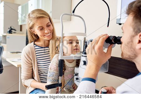 Portrait of cute little girl siting on mothers lap  and looking at slit lamp machine during medical check up in eye clinic
