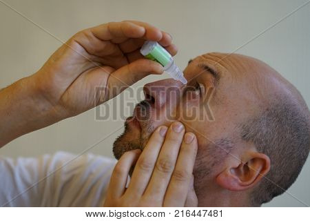 Young Bald Man Sick From Common Cold Flu Blowing His Nose With Paper Tissue