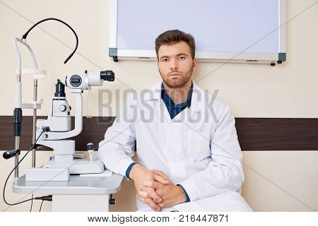 Portrait of male ophthalmologist sitting at slit lamp machine while posing looking at camera confidently