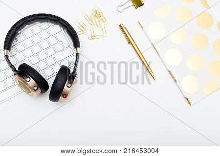 Gold headphones and keyboard on white background. Flat lay