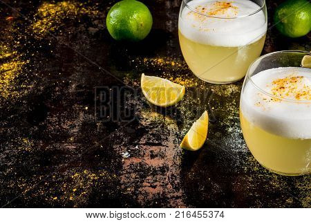 Peruvian Mexican Chilean traditional drink pisco sour liqueur with fresh lime on rusty black table copy space