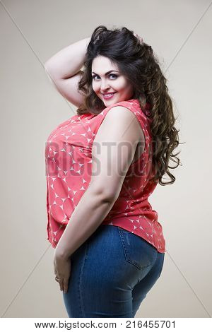Happy plus size fashion model in casual clothes sexy fat woman on beige studio background