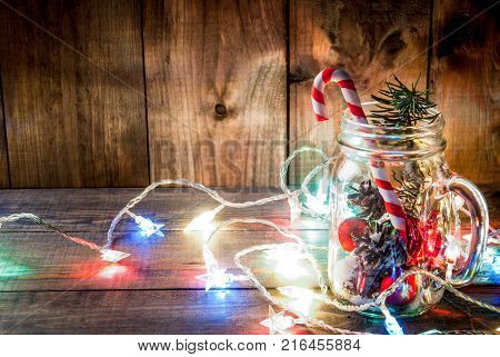 Christmas New Year's concept. Mason Jar with Christmas decorations fir cones artificial snow candy cane and fir branch. On a wooden table background with a lit garland turned on. Copy space