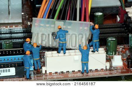 Motherboard Repair - Miniature construction worker figurines posed as if working on a computer motherboard.