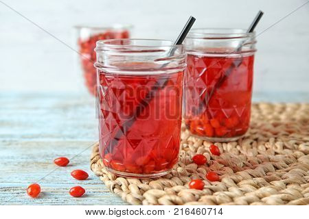 Mason jars with healthy goji juice on wooden table