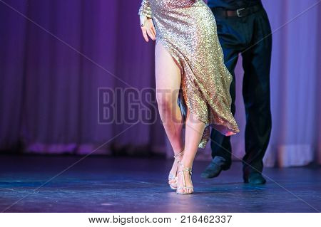 performing, competition, fashion concept. slim legs of dancing couple, man and woman, she dressed in amazing dress that shining in the spotlights with charming high slit