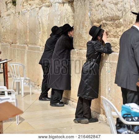 Orthodox hasidic religious jews dressed in black traditional outfit pray at the wailing wall during the high holidays in jerusalem israel