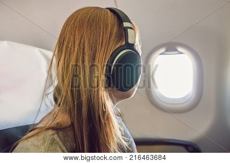 Passenger In Airplane Using Headphones. Woman In Plane Cabin Listening To Music On Headphones.