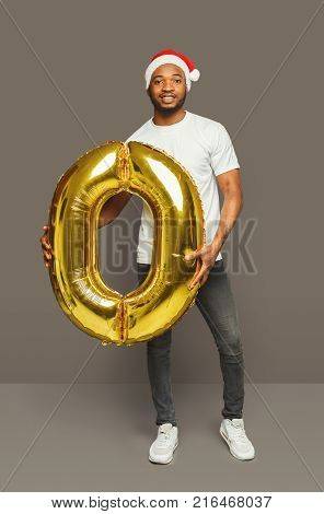Happy black man with number 0 balloon portrait. African-american boy in santa hat at studio background. One of shots to compose 2018 for new year and christmas greeting card