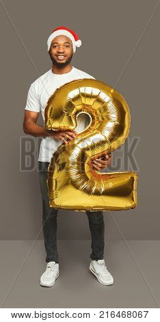 Happy black man with number 2 balloon portrait. African-american boy in santa hat at studio background. One of shots to compose 2018 for new year and christmas greeting card