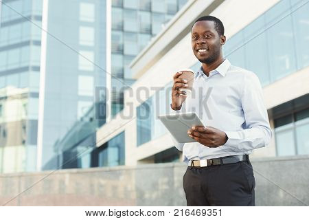 Confident successful black businessman with tablet outdoors. African-american executive taking a city walk at lunch time, drinking take away coffee at urban area background