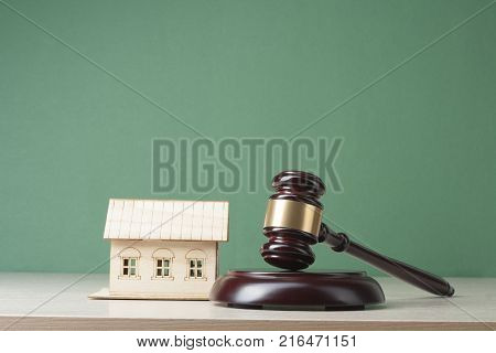 Model house and judge gavel on wooden table. Law and property concept