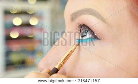 Make-up artist applying make-up to model's eye. Redhead model at make up procedure, close up view.