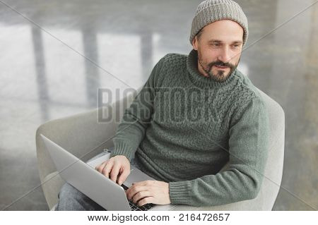 Indoor Shot Of Professional Bearded Middle Aged Male Wears Knitted Sweater And Hat, Sits In Front Of