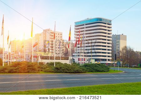 Flags countries near roadway against backdrop large modern business office building