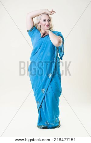 Plus size fashion model sexy fat woman in saree on beige studio background full length portrait