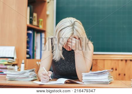 difficult work of the teacher. The teacher bowed his head over the control works of the students