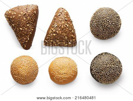 Buns and rolls assortment at white background. Triangle rye buns with sunflower seeds, black and white humburger buns with sesame. Flat lay, top view, isolated
