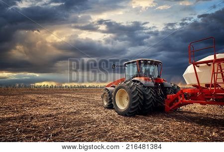 Tractor working on the farm, a modern agricultural transport, a farmer working in the field, fertile land, tractor on a sunset background, cultivation of land, agricultural machine