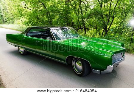 NEVINOMYSSC, RUSSIA - MAY 13, 2016: Automobiles. Offsite photography of old American cars. Oldsmobile 98s. View of Machine type on the side on a country road in a green forest