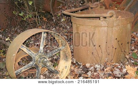 Rusty old metal bucket and wheel laying in field
