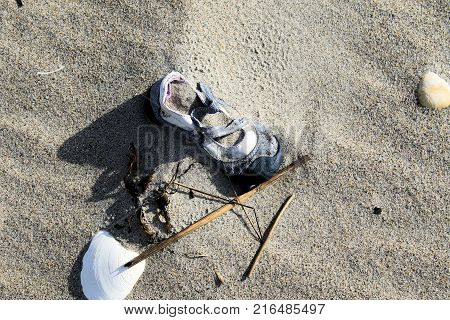 Lost and forgotten child's shoe half buried in beach sand.