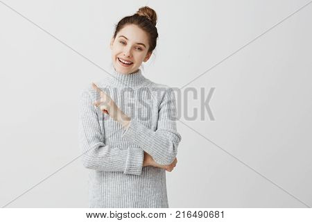 Happiness and enjoy concept. Beautiful adult girl showing at great thing with wide smile. Female enthusiast presenting her preference with finger gesture