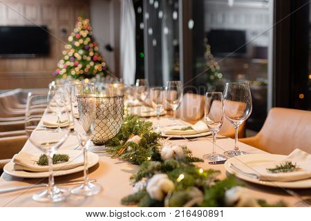 Christmas dinner feast. A decorated dining table with champagne glasses and christmas tree in background.