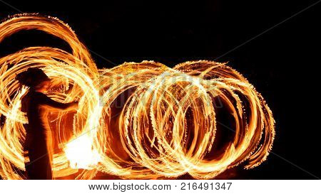 Fire poi show in the dark with blurred performer