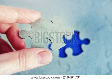 Hand holding piece of puzzle with the last missing piece. Business Concept of successful completion of a job